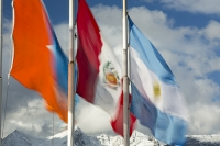 Ushuaia;Tierra-del-Fuego;Argentina;Patagonia;South-America;Austral;town;South;southerly;red;tourism;Isla-Grande-de-Tierra-del-Fuego;Beagle-Channel;Martial-Mountain-Range;travel;flag;Argentinian-flag;patriotism;wind;windy;flap;flapping;movement;blur;motion-blur;fabric;red;blue;orange;colourful;weather;peak;snow;mountain