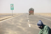 China;climate-change;global-warming;dry;drought;water;water-shortage;earth;soil;desertificatiion;Inner-Mongolia;dessication;road;highway;visibility;sand;sand-storm;erosion;man;chinese;cyclist;smog;smoke-mask;face-mask;protection;air-pollution