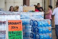 USA;US;America;California;drought;climate-change;global-warming;Central-Valley;San-Joaquin;Porterville;run-dry;run-out;charity;water-chairty;bottled-water;well;desperate;plastic;blue;man;male;help;charity-worker;volunteer;volunteering;care;compassion;help;assistence;loading;sign;well;dry-well;composite
