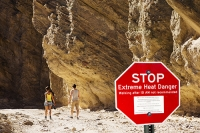 California;USA;America;Death-Valley;desert;drought;hot;dry;low;heat;National-Park;preserved;protected;dessicated;barren;mountain;mountain-range;geology;rocks;sand;sandy;badlands;gully;gulch;erosion;weathering;layer;layering;bedding;scenery;landscape;blue;sky;cloud;red;red-rocks;red-canyon;red;warning;warning-sign;extreme-heat;walker;wallking;trail;couple;man;women;tourist;tourism;composite;red;sign;warning;danger;extreme-heat