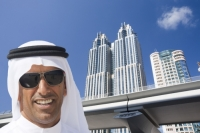 Dubai;Middle-East;arabic;high-rise;tower-block;development;luxury;wealthy;expensive;architecture;design;construction;building;building-site;Emirates;tower;glass;glass-fronted;reflection;man;male;arab;arabic;white;robe;sunglasses;face;teeth;smile