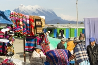 South-America;Bolivia;fabric;bolt;cloth;colourful;rainbow;red;blanket;identity;pride;national;shop;for-sale;print;printed;woven;weaving;art;La-Paz;El-Alto;market;market-stall;retail;street-scene;woman;Indigenous;native;national-costume;shawl;Illimani;backdrop;mountain;snow;snow-capped;glacier;glacial-retreat;climate-change;global-warming