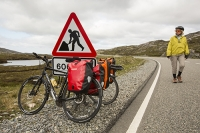 Isle-of-Harris;Outer-Hebrides;Scotland;UK;road;North-Harris;hilly;mountain;mountainous;rugged;rocky;barren;road;main-road;route;woman;female;fit;exercise;travel;vacation;holiday;cycling;helmet;cycling-helmet;route;hilly;pannier;load;road-sign;road-works;red