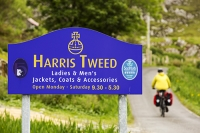 Harris;Isle-of-Harris;Outer-Hebrides;Hebrides;Scotland;UK;remote;peat;bike;bicycle;cycling;panniers;load;cycle-touring;road;woman;female;Golden-road;East-Coast;rugged;remote;barren;rocky;Harris-Tweed;sign;advert;blue;pannier;load