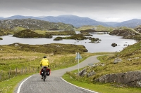 Harris;Isle-of-Harris;Outer-Hebrides;Hebrides;Scotland;UK;remote;peat;bike;bicycle;cycling;panniers;load;cycle-touring;road;woman;female;Golden-road;East-Coast;rugged;remote;barren;rocky;pannier;load;lochan;loch