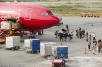 Kangerlussuaq;Greenland;C02;carbon-footprint;global-warming;climate-change;flight;flying;plane;jet;Air-Greenland;red;freight;passenger;suitcase;luggage;baggage;baggage-handler;airport;airport-worker;worker;moving;goods;import;export;runway;tarmac;tourist;tourism
