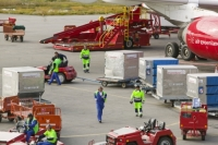 Kangerlussuaq;Greenland;C02;carbon-footprint;global-warming;climate-change;flight;flying;plane;jet;Air-Greenland;red;freight;passenger;suitcase;luggage;baggage;baggage-handler;airport;airport-worker;worker;moving;goods;import;export;runway;tarmac;tourist;tourism;protective-clothing;high-vis;high-visibility