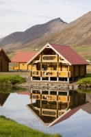Iceland;Northern-Iceland;Olafsfjordur;town;house;housing;hill;slope;mountain;steep;building;colouful;hill-summer;mountain-range;sky;cloud;lake;water;reflection;still;reflected;cabin;log-cabin;wood;wooden;wooden-cabin;lodge;holiday-home;chalet;timber;timber-chalet