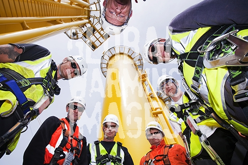 Workers at the Walney Offshore Wind farm, Barrow in Furness, Cumbria, UK, in front of wind turbine transition pieces. The windfarm was constructed and is owned by the Danish, Dong Energy company. It has the capacity to generate 367MW. Converting to a renewable future creates many green, sustainable jobs.