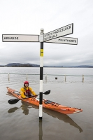 sea;sea-front;promenade;damage;destruction;storm-damage;Irish-sea;climate-change;global-warming;shingle;seafront;High-Street;power;powerful;weather;extreme-weather;storm-surge;infrastructure;road;flooded-road;Sandside;Storth;Arnside;Kent-estuary;Morecambe-Bay;high-tide;flood-waters;inundated;salt-water;tidal;tidal-surge;pedestrian;onlooker;observer;canoe;canoeist;kayak;kayaker;kayaking;paddle;paddling;sign;road-sign;orange;man;male