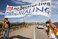 tar-sand;tar-sands;oil-sand;oil-sands;oil-industry;fossil-fuel;climate-change;global-warming;industry;heavy-industry;industrial;Athabasca;Alberta;Canada;Indian;First-Nation;Healing-Walk;protest;protesting;heal;destruction;banner;start;stop;breathing-mask;pollution;contamination;contaminated;strip-mining;Syncrude;Fort-McMurray;dress;traditional;sky;environment;environmental-destruction;carbon-footprint;statement;female;woman;affected;Boreal-Forest;sky;blue;toxic;tailings-pond;oil;bitumen;deposits;oil-reserves;smog;air-pollution;chimney;smoke-stack;emissions;carbon-footprint;flag;solidarity;road;highway;highway-63