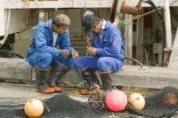 fishing;fishing-nets;net;fisherman;fishermen;mending;repair;sea-fish;Inuit;Eskimo;men;male;worker;Ilulissat;Greenland;harbour;boiler-suit;blue;float;trawler;boots;wellington-boots