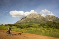 Africa;Malawi;rrural;countryside;peak;hill;kopje;sky;blue;cloud;woodland;granite;rock;geology;tree;green;rainy-season;Mulanje;mountain;road;dirt-track;off-road;soil;track;man;male;bike;bicycle;cycling;transport
