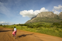 Africa;Malawi;rrural;countryside;peak;hill;kopje;sky;blue;cloud;woodland;granite;rock;geology;tree;green;rainy-season;Mulanje;mountain;road;dirt-track;off-road;soil;track;woman;female;bike;bicycle;cycling;transport