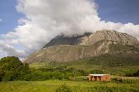 Africa;Malawi;rrural;countryside;peak;hill;kopje;sky;blue;cloud;woodland;granite;rock;geology;tree;green;rainy-season;Mulanje;mountain;house;brick;cliff;sheer;steep;granite;cliff-face;woodland;forest