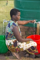 Malawi;Africa;Chiteskesa;refugee-camp;flood;floods;flooding;displaced;charity;NGO;aid;female;woman;black;African;green;dress;women;disaster;disaster-relief;climate-change;global-warming;refugee;poor;poverty;water;water-tan;water-supply;clean-water