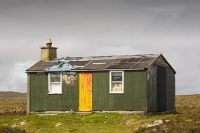Lewis;Isle-of-Lewis;Outer-Hebrides;hebrides;Scotland;UK;Stornoway;cabin;hut;old;derelict;decay;weathered;peat;peat-bog;peat-cutting;green;door;window;orange;shed;house