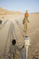 Egypt;Sinai;desert;sinai-desert;Dahab;Red-Sea;animal;mammal;Camel;beast-of-burden;arab;arabic;nomad;nomadic;desert-dweller;Bedouin;culture;wealth;caravan;tourism;tourist-trade;trip;camel-ride;domesticated;trek;saddle;camel-ride;camel-riding;woman;tourist;tourist-trip;hat;shadow;dusk;evening;child
