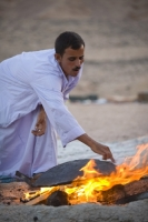 Egypt;Sinai;desert;sinai-desert;Dahab;Red-Sea;sand;sandy;rocky;outcrop;sky;night;sky;star;bedouin;arab;arabic;guide;light;camp;camping;nomad;nomadic;lifestyle;culture;arab;arabic;man;male;fire;cook;cooking;bread;prepare;meal;flame