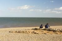 cley;Norfolk;UK;North-Norfolk;coast;tidal;beach;shingle;flint;cobble;sign;warning;damage;flood-surge;storm-surge;concrete;person;couple;two