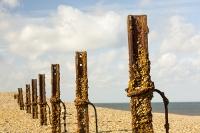 cley;Norfolk;UK;North-Norfolk;coast;tidal;beach;shingle;flint;cobble;damage;flood-surge;storm-surge;person;walker;walking;breach;breached;storm-beach;inundated;wildlife-reserve;bird-reserve;rust;rusty;rusting;second-world-war;defences;post;iron;metal