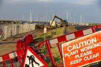 Blakeney;Norfolk;UK;North-Norfolk;coast;tidal;tidal-flooding;flood-surge;boat;damage;JCB;plant;digger;sea-wall;levee;protection;coastal-protection;coastal-defences;defences;repair;repairing;storm-damage;fence;sign;red;caution