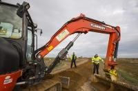 Blakeney;Norfolk;UK;North-Norfolk;coast;tidal;tidal-flooding;flood-surge;boat;damage;sea-wall;levee;protection;coastal-protection;coastal-defences;defences;repair;repairing;storm-damage;Environment-Agency;soil;brown;orangw;digger;JCB;plant;caterpiller-tracks;workman;high-vis;PPE;health-and-safety