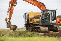 Norfolk;UK;North-Norfolk;coast;tidal;damage;flood-surge;storm-surge;person;walker;walking;breach;breached;storm-beach;inundated;wildlife-reserve;bird-reserve;Titchwell;RSPB;sea-wall;levee;repair;repairing;digger;plant;JCB;orange;bucket;hydraulic