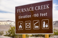 California;USA;America;Death-Valley;desert;drought;hot;dry;low;heat;National-Park;preserved;protected;mud-cracks;lake-bed;dessicated;barren;mountain;mountain-range;geology;rocks;sand;sandy;Furnace-Creek;visitor-centre;sign;notice;National-Park-Service;elevation;below-sea-level;sea-level