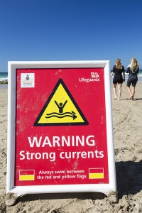 Cornwall;UK;coast;plant;St-Agnes;sea;cliff;sea-cliff;summer;sign;yellow;South-west;warm;cove;beach;Coast-guard;life-guard;vehicle;four-wheel-drive;surfing;surf-board;pebble;sand;Chapel-Porth;red;warning;currents;strong-currents;danger;woman;female;two;couple;friends;wetsuit